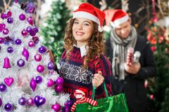 Beautiful Woman Carrying Shopping Bag At Christmas. Portrait of beautiful young women carrying shopping bag at Christmas store with men in background Royalty Free Stock Photography