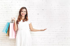 Beautiful woman carrying shopping bags while presenting copy spa. Portrait of beautiful woman carrying shopping bags while presenting copy space with white brick Royalty Free Stock Photography