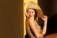 Beautiful woman in a casual clothes and hat. Looking at camera and smiling. Yellow background, outdoor Stock Photography