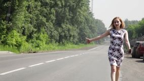 Beautiful woman catching car on a road. girl walking along the road stock video