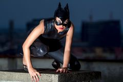 Woman in cat costume. Beautiful woman in catwoman leather latex on the roof Royalty Free Stock Photo