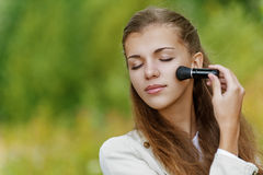 Beautiful woman causes powder. Young beautiful woman with closed eyes causes powder to face, against background of autumn park Royalty Free Stock Photo