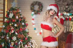 Beautiful woman celebrates Christmas at home in the interior wit royalty free stock photography