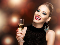 Beautiful woman celebrating with campaign; dark background Stock Photo