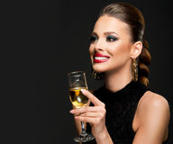 Beautiful woman celebrating with campaign; dark background Stock Photos