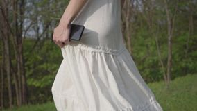 Beautiful woman with cellphone in long white skirt and jeans jacket walking through forest close up. Camera moving from stock footage