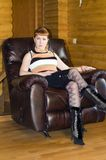 Beautiful woman in the chair. Beautiful woman sitting in the leather chair Royalty Free Stock Photo
