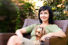 Beautiful woman in chair with little dog in garden Stock Photography