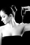 A beautiful woman with a champagne glass. A black and white image of a beautiful woman with a champagne glass on her shoulder Royalty Free Stock Images