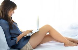A beautiful woman is chatting with her friends on her bed by using her laptop stock photos