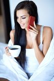 Beautiful woman chatting on a mobile in bed Royalty Free Stock Images