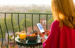 Woman chatting on phone at breakfast on terrace royalty free stock photography