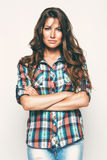 Beautiful woman in check shirt and jeans. In studio Royalty Free Stock Images
