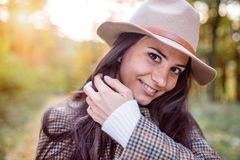 Beautiful woman in checked coat and hat, autumn forest Royalty Free Stock Images