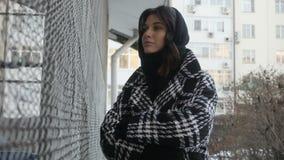 Woman in coat near net fence stock video