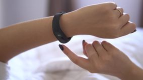 Beautiful woman checking data on her fitness tracker band after waking up in the bed early morning. He is watching