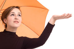 Beautiful woman checking if it's raining. From underneath an orange umbrella isolated over white background Royalty Free Stock Photo