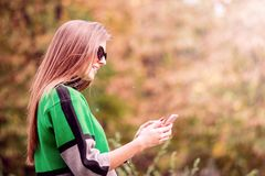 Beautiful woman checking phone. Beautiful woman checks  messages on her mobile phone in the park Stock Image