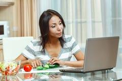 Beautiful woman checks the recipe. Using computer Stock Photo