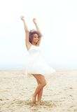 Beautiful woman with cheerful expression dancing at the beach in white dress Royalty Free Stock Photos