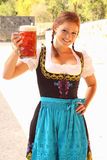 Beautiful Woman Cheering with Beer. Beautiful red-head woman wearing a traditional bavarian dirndl dress cheering with a beer mug Royalty Free Stock Images