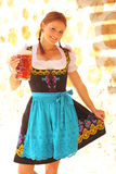 Beautiful Woman Cheering with Beer. Beautiful red-head woman wearing a traditional bavarian dirndl dress cheering with a beer mug Stock Photography