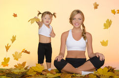 Beautiful woman and child do yoga under leaves Royalty Free Stock Photography