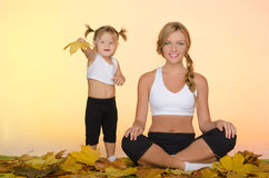 Beautiful woman and child doing yoga in fall Royalty Free Stock Images