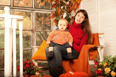 Beautiful woman with a child on the front porch with pumpkins au Royalty Free Stock Photo