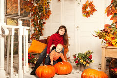 Beautiful woman with a child on the front porch with pumpkins au Royalty Free Stock Images