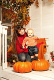 Beautiful woman with a child on the front porch with pumpkins au Stock Photography