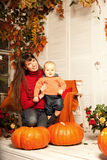 Beautiful woman with a child on the front porch with pumpkins au Royalty Free Stock Image