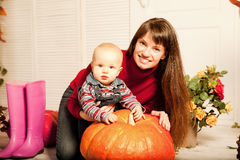 Beautiful woman with a child on the front porch with pumpkins au Stock Images