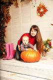 Beautiful woman with a child on the front porch with pumpkins au Royalty Free Stock Photos