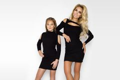 Beautiful woman with a child inspring clothes. Mom and daughter on a photo session stock photography