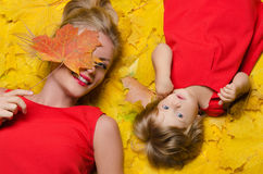 Beautiful woman and child on yellow autumn leaves Stock Image