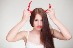 Beautiful woman with chili pepper devil horns. Beautiful woman holding chili pepper like devil horns stock image