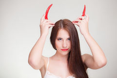Beautiful woman with chili pepper devil horns. Beautiful woman holding chili pepper like devil horns stock photo