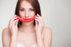 Beautiful woman with chili pepper smile. Beautiful woman holding chili pepper like smile Royalty Free Stock Photography