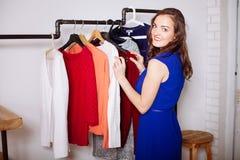Beautiful woman chooses clothes in the wardrobe closet stock photos