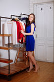 Beautiful woman chooses clothes in the wardrobe closet. Young woman chooses clothes in the wardrobe closet royalty free stock images