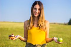 Beautiful woman choosing between apple and donut royalty free stock images