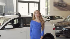 Beautiful woman choosing automobile to buy at dealership salon. Charming elegant businesswoman walking at auto dealership, smiling to the camera. Cars concept stock footage