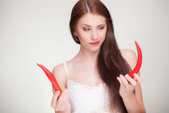 Beautiful woman choosing from chili peppers. Beautiful woman choosing from two chili peppers Stock Image
