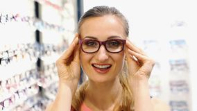 Beautiful woman choosing new glasses in store stock video footage