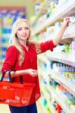 Beautiful woman choosing personal care product in supermarket Stock Images