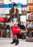 Beautiful woman choosing red leather bag Stock Photography