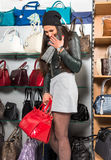 Beautiful woman choosing red leather bag Stock Photo