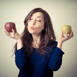 Beautiful woman choosing red or yellow apples Royalty Free Stock Photos