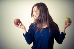 Beautiful woman choosing red or yellow apples Stock Photos